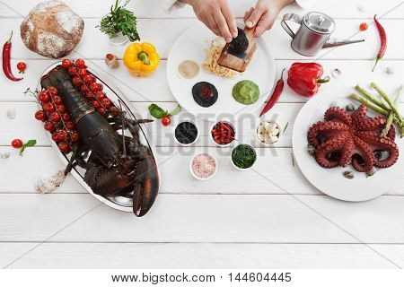 Chef spreading italian traditional meal of pasta and ravioli with black truffle, flat lay, copy space, white wooden background. Italian cuisine, culinary classes, restaurant kitchen concept