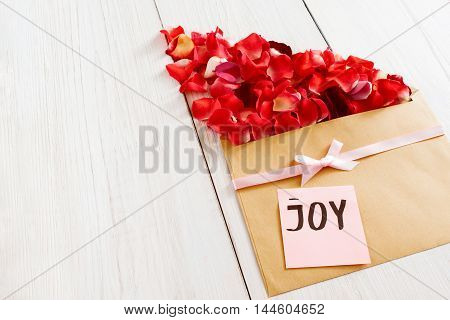 Floral present with rose petals and joy text, copy space. Beautiful greeting composition made from red flower bloom and brown kraft envelope on white wooden background