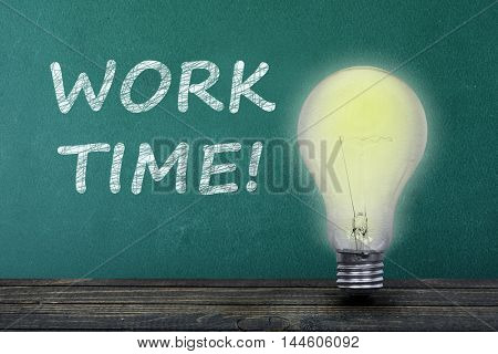 Work Time text on green board and light bulb on table