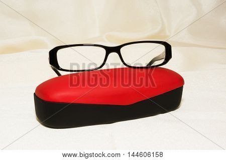 Glasses with black frames and red case