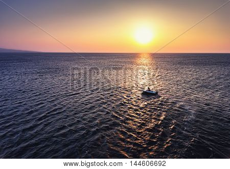 Aerial view over Fishing boat on the water and beautiful sunrise