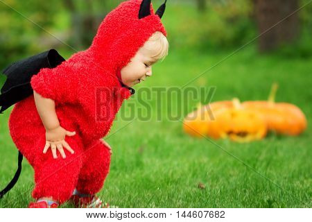 Baby in devil costume with pumpkins. Child in halloween outfit playing in the garden