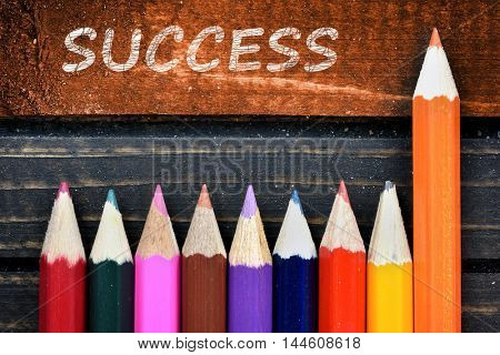 Success text and group of pencil on wooden table