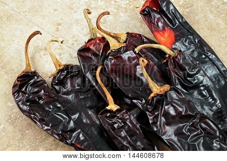 Large, dried poblano peppers on a rustic background