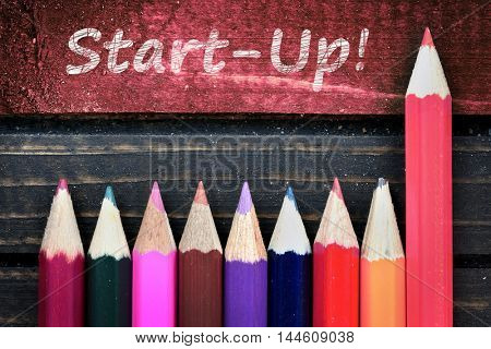 Start-up text and group of pencil on wooden table