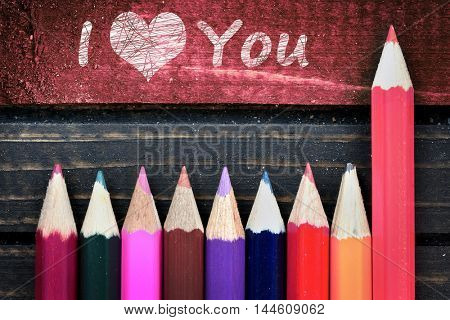 I love you text and group of pencil on wooden table