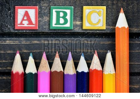 ABC text and group of pencil on wooden table