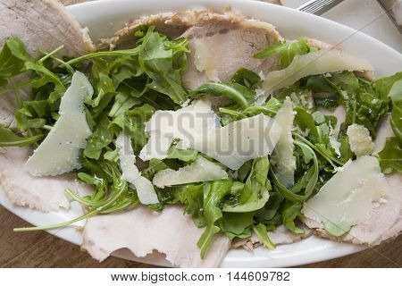 roast chine of pork served with arugula and parmesan cheese