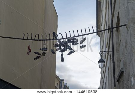 PARIS, FRANCE - MAY 11, 2016: Old shoes hang on the iron bars. Looks like a stupid teenager joke.  Latin Quarter in Paris, France.