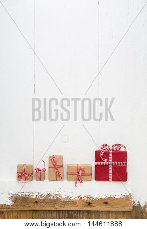 Five christmas presents on wooden white background in red colors for concepts.