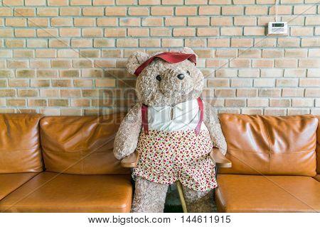 Cute teddy bear sitting on chair