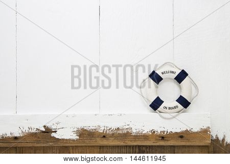 Welcome on board. Old wooden shabby background with a safety buoy for traveling or business concepts.