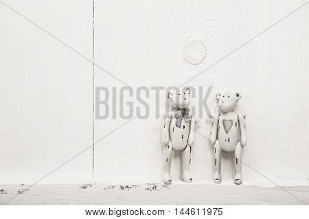 Two old shabby chic nostalgic teddy bears on white wooden background for love and wedding concepts.