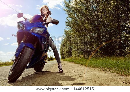Sexy young woman biker sitting on her motorcycle on a road. Beauty, fashion. Adventure concept.
