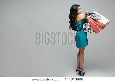 Let's go shopping happiness, consumerism, sale and people concept - smiling young woman with shopping bags
