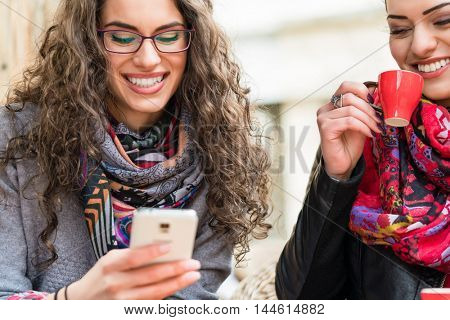 Young women having coffee and laughing about pictures on smart phone