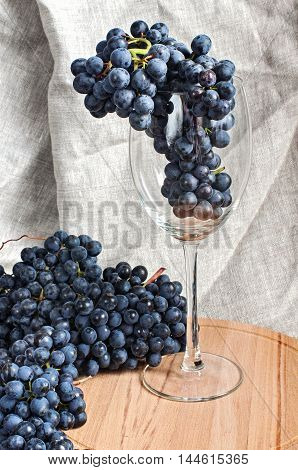 Bunch of Grapes in wine glass on wooden tray