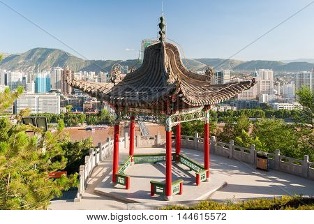 Pavilion in the Baitashan Park in Lanzhou with skyline of the city in background