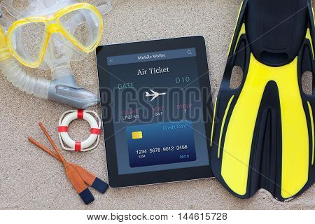 tablet computer with online air ticket on sand with fins and snorkel