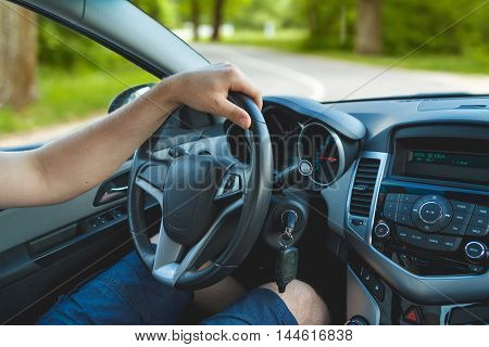 Young man driving a car. Close-up of a steering wheel