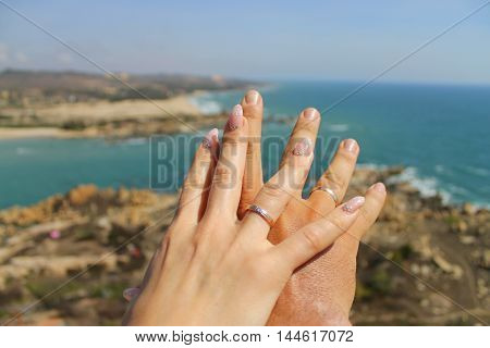 Hands of just married crossed with rings on fingers with the sea as background in honeymoon