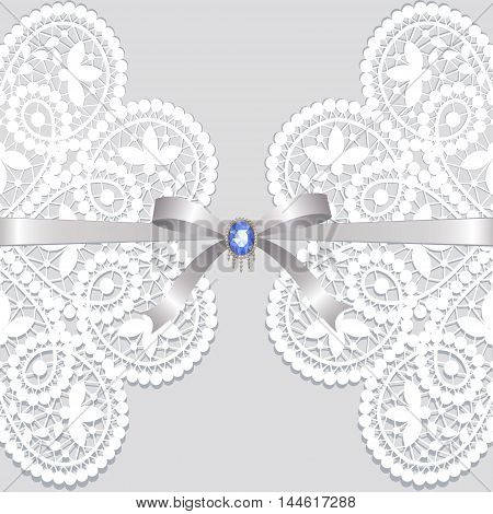 White lace with ribbon and jewelery on a gray background