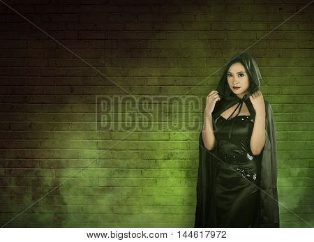 Asian witch woman in empty room with green fog she wearing black costume