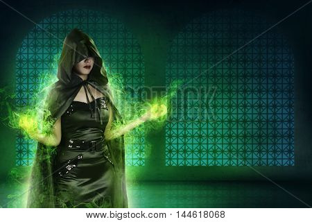 Asian Witch Woman Wearing Black Costume In Empty Room. Her Hand Gesture Out Of Green Light
