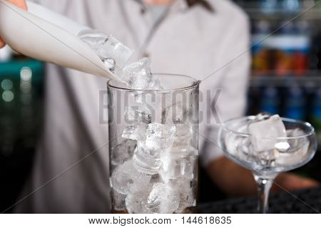 Barman's hands in bar interior making alcohol cocktail. Professional bartender at work in bar pouring ice into glass for drink. Party time in night club