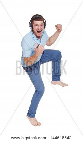 Happy young man with headphones sing, dance and enjoy loud sound of music, isolated at white background. Young guy in blue t-shirt listens music from his mobile smartphone with wireless earphones.