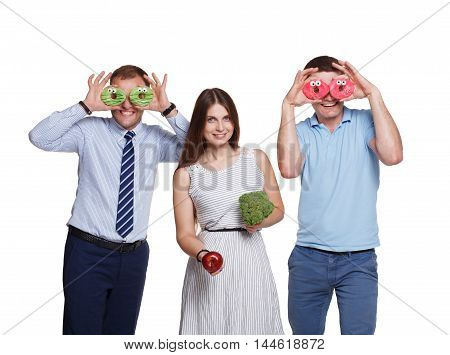 Studio shot of young men make donut glasses and woman shows broccoli and apple. Healthy or junk food, diet or sweets concept. Isolated at white background.