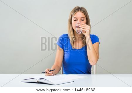 Beautiful female student is drinking water while studying.