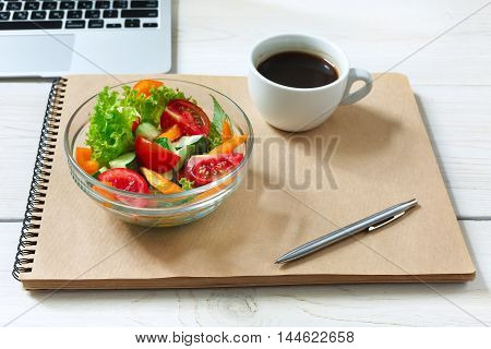 Healthy business lunch in office, vegetable salad bowl on white wooden desk and notepad with pen. Organic meal and americano coffee cup. Snack at break time