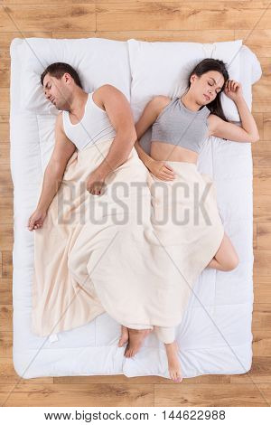 Wedded pair. Top view of tired young couple having pleasant sleep in bed lying under blanket