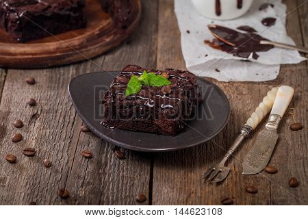 Cake chocolate brownies with dark chocolate  dressing and mint on wooden table
