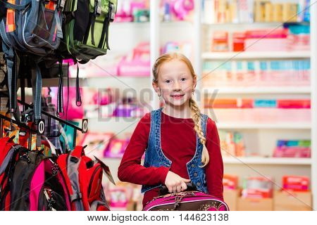 Child choosing satchel for her first day in school in stationery store