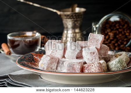 Cup of coffee with turkish delight on oriental plate on black wooden background