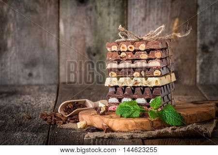 An assortment of white, dark, and milk chocolate with nuts and with various fillings on wooden background
