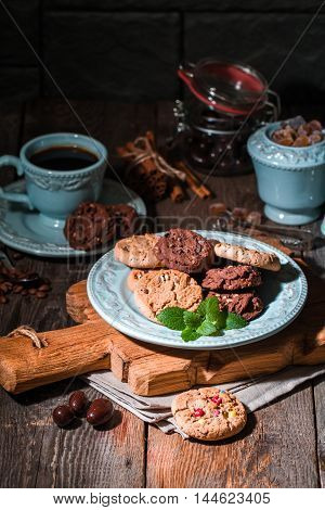 Chocolate chip cookies on plate with coffee on dark wooden table.