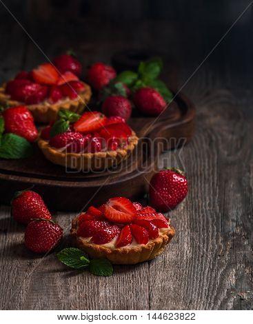 Fresh homemade strawberries tarts  on wooden background