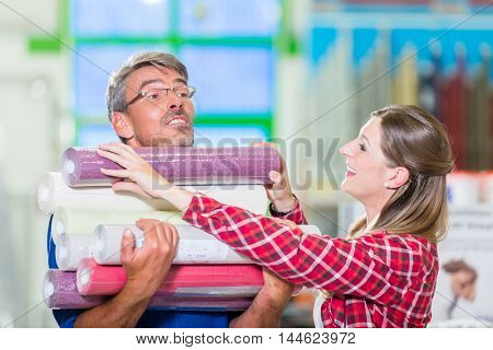 Home improving couple, woman and man, buying many rolls of wallpapers at hardware store for do-it-yourself project