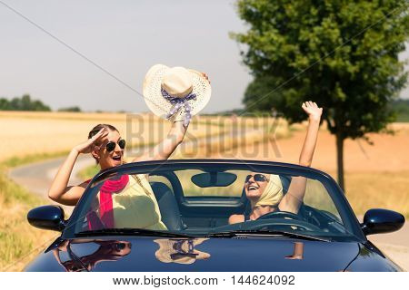 Best friends having summer joyride in convertible car passing a field