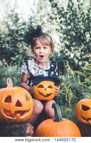 Halloween. Child dressed in black with jack-o-lantern in hand trick or treat. Little girl with pumpkin in the wood outdoors. Wow. Toned photo.