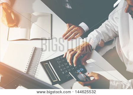 Top view of two businesspeople working together at one desk. One is calculating. Second is making notes. Concept of accounting