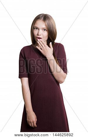 Isolated portrait of astonished girl in red dress with long light hair standing with her hand near open mouth. Concept of gossip and rumors