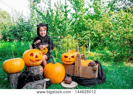 Halloween. Child Dressed In Black With Jack-o-lantern In Hand, Trick Or Treat. Smiling Little Girl