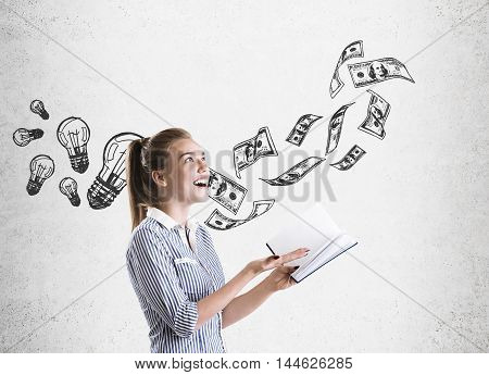 Smiling girl in striped shirt standing near concrete wall with dollar notes and light bulb sketches. Concept of making money from air.