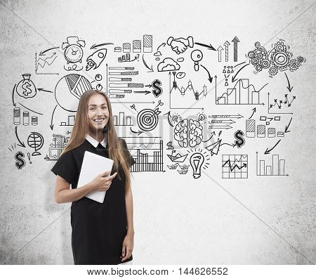 Smiling young business lady standing near concrete wall with startup sketches. Concept of brainstorm