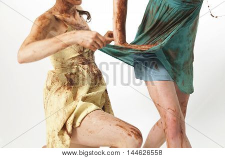 Woman Pulling Her Friends Dress Dirtied In Chocolate