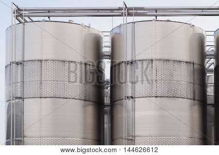 Three wine blending tanks glisten in the afternoon sun.